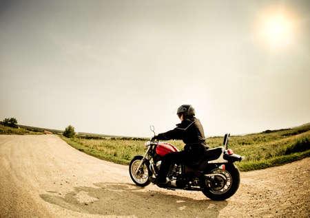 motor race: Biker op de landweg tegen de hemel