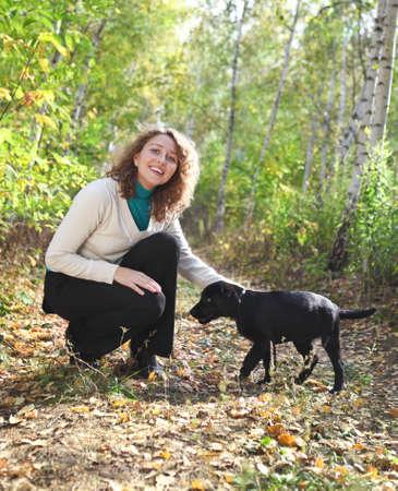 mujer con perro: Mujer joven que juega con el perrito negro de Labrador retriever en el bosque de otoño Foto de archivo