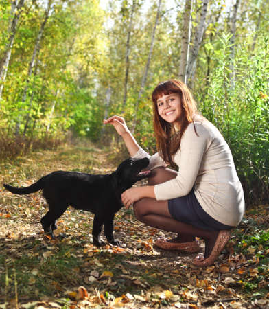 Teenager girl with black labrador retriever puppy outdoors Stock Photo - 16606186