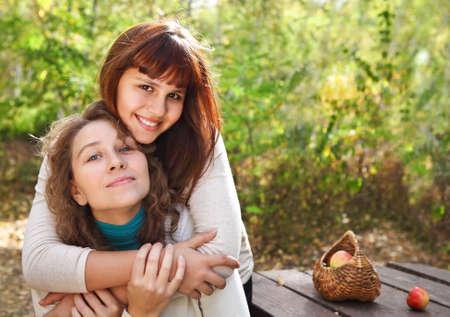 madre e hija adolescente: Mujer joven sonriente con sus hijas adolescentes al aire libre