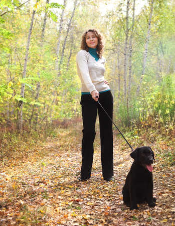 Young woman walking with black labrador retriever puppy in the autumn forest Stock Photo - 16606154