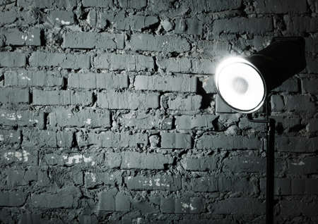 Studio flash near the gray damaged brick wall Stock Photo - 16657345