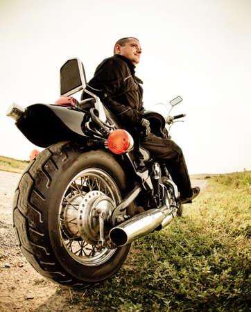 chaqueta de cuero: Motorista en el camino rural en el cielo