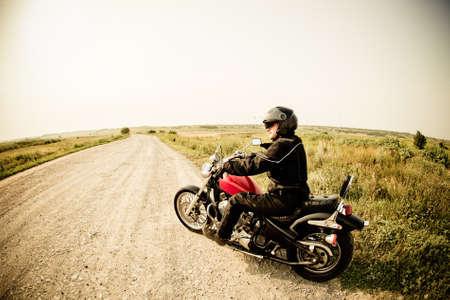 motociclista: Biker sulla strada di campagna contro il cielo Archivio Fotografico