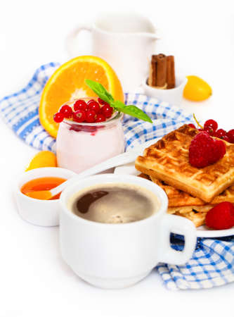 Delicious breakfast with fresh coffee, fresh waffles and fruits. Over white background  photo