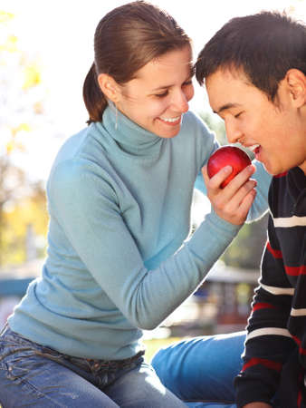 Happy young couple in love with apple outdoors Stock Photo - 16789462