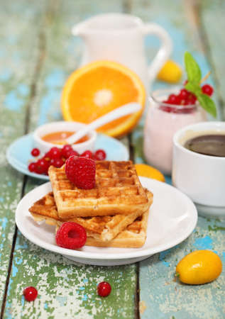 Delicious breakfast with fresh coffee, fresh waffles and fruits. Over rustic background  photo