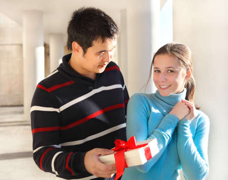 Happy young couple in love with present outdoors photo