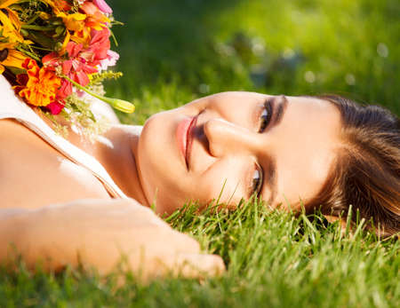 Beautiful young girl relaxing on green grass in summer park Stock Photo - 16891472