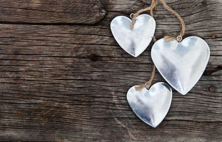 Metal hearts on wooden background. Valentine`s day concept photo