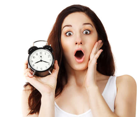 Surprised young brunette woman holding clock in her hand in amazement photo