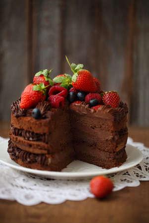 rebanada de pastel: Trozo de pastel de chocolate con bayas frescas y la formaci�n de hielo en el fondo de madera Foto de archivo
