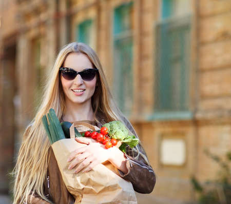 Young happy woman with shopping bag outdoors photo