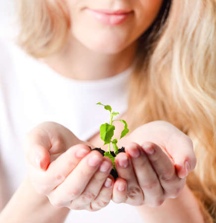 Young woman holding young plant in her hands. Shallow depth of field Stock Photo - 17052721