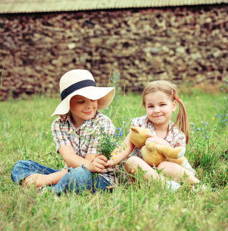 Little boy gives flowers to the little girl near the country house photo