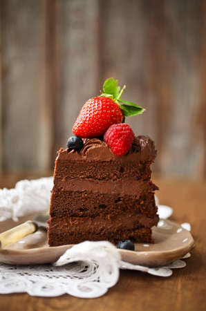 chocolate slice: Piece of chocolate cake with icing and fresh berry on wooden background Stock Photo
