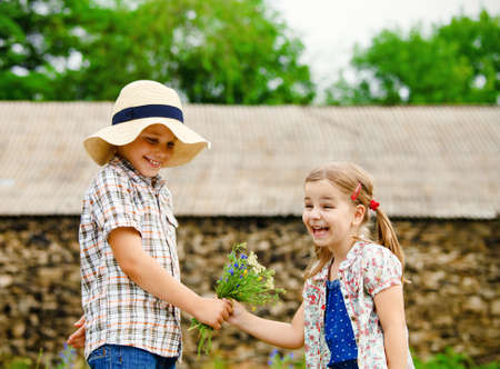 girl holding flower: Little boy gives flowers to the little girl near the country house