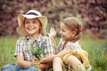 country boy: Little boy gives flowers to the little girl near the country house