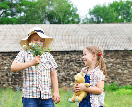 gives: Little boy gives flowers to the little girl near the country house