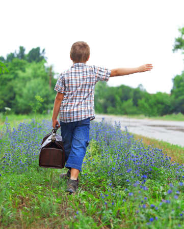lonely road: Little boy with suitcase standing about road  Stock Photo