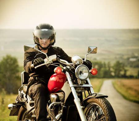 motociclista: Motorista en el camino rural en el cielo
