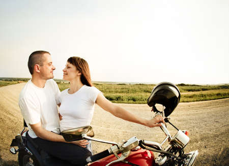 woman motorcycle: Young biker couple on the country road against the sky