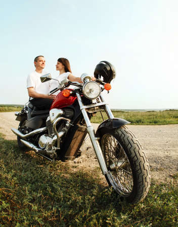 Young biker couple on the country road against the sky photo