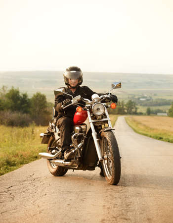 country side: Biker on the country road against the sky Stock Photo