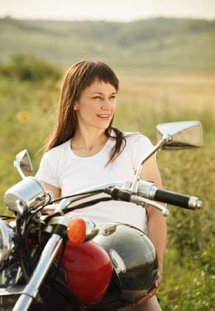 Young biker woman on the country road against the sky photo