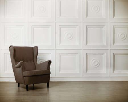 cadeira: Uma poltrona clássica contra uma parede branca e no chão. Espaço para texto
