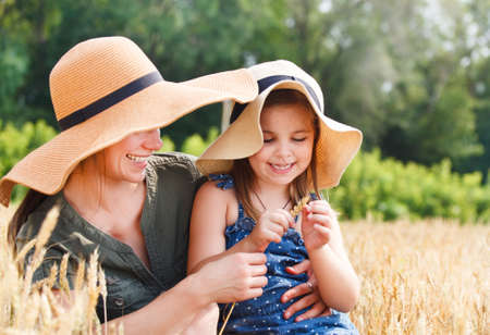 Happy mother and her little daughter in the wheat field photo