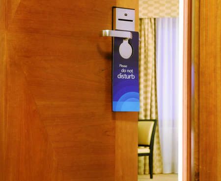 Please do not disturb sign hanging on open door in a hotel photo