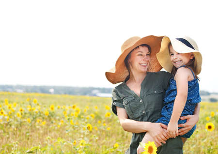 Happy mother and her little daughter in the sunflower field photo
