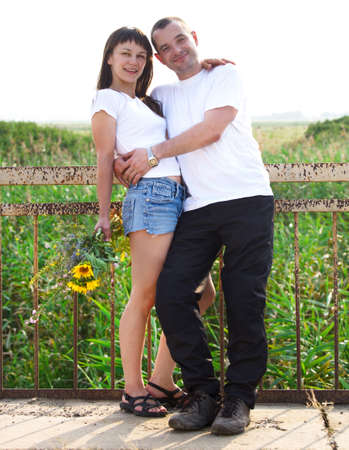 Happy young smiling couple with flowers outdoors Stock Photo - 17527375