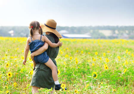 mother's hand: Happy mother and her little daughter in the sunflower field