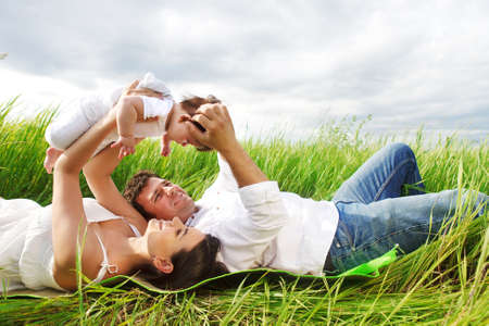 family baby: Happy young family with little baby girl outdoors Stock Photo