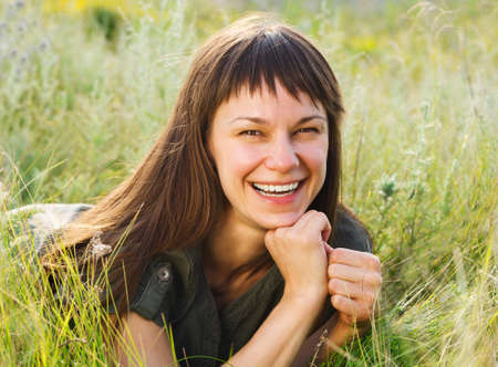 medow: Smiling brunette woman on medow in summer day Stock Photo
