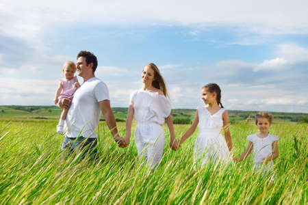 man field:  Happy young family with three children outdoors