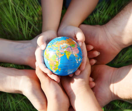 Earth in hands of the family against green grass blurred background photo