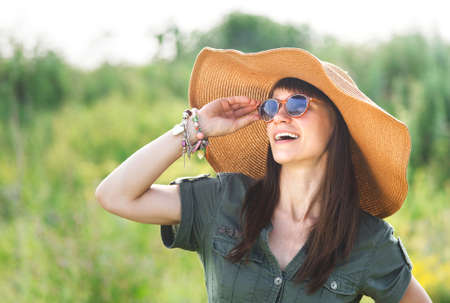 Smiling brunette woman in hat in summer day photo