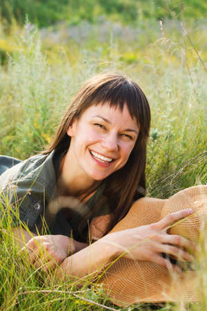Smiling brunette woman with hat in summer day photo