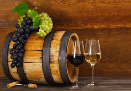 old bar: Still life with glasses of red and white wine, barrel with grapes Stock Photo