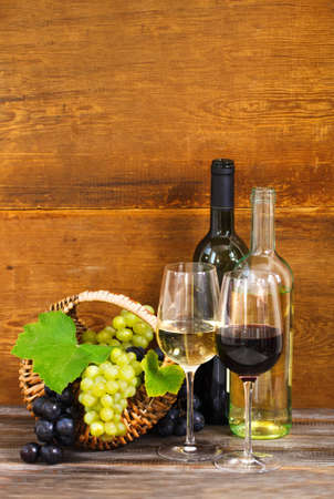 intoxicant: Still life with red and white wine, bottles and basket with grapes