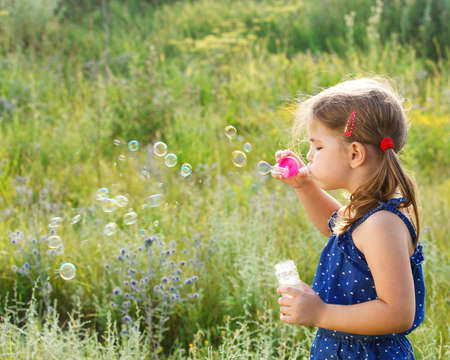girl blowing: Little cute girl blowing soap bubbles outdoors