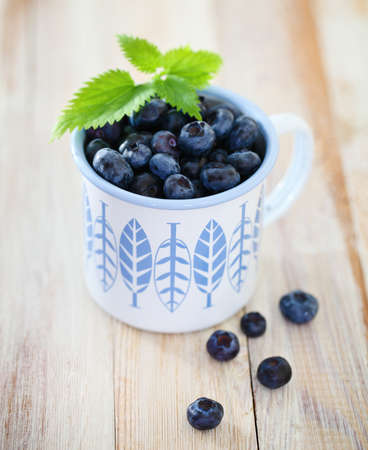 Delicious fresh blueberry in the white and blue cup on the table photo