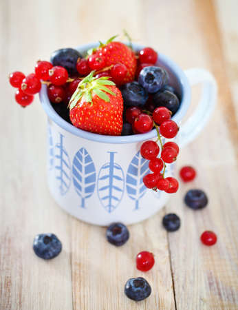 Delicious fresh fruits in the white and blue cup on the table photo