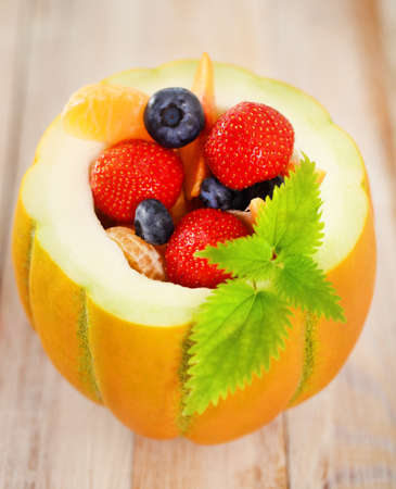 Delicious fresh fruits served in melon as dessert photo