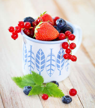 fruity salad: Delicious fresh fruits in the white and blue cup on the table