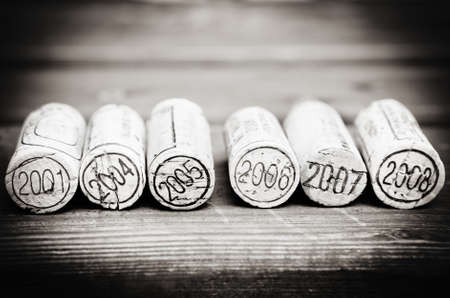 dated: Dated wine bottle corks on the wooden background. Black and white Stock Photo