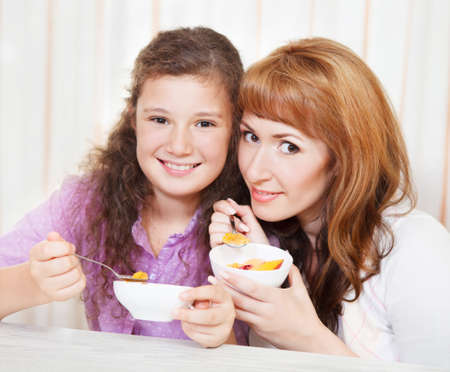 Happy mother and daughter eating cereal and fruit photo